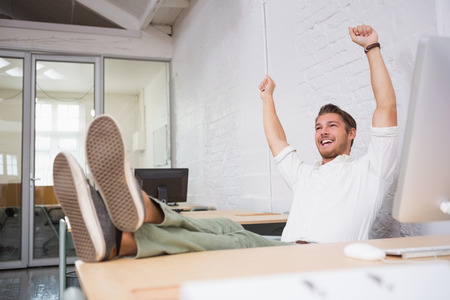 Full length of cheerful businessman cheering in the office photo