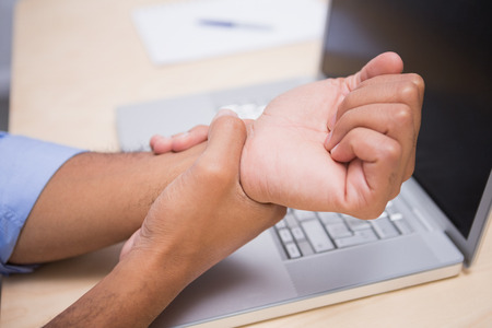 Close up of businessman suffering from wrist pain in office photo