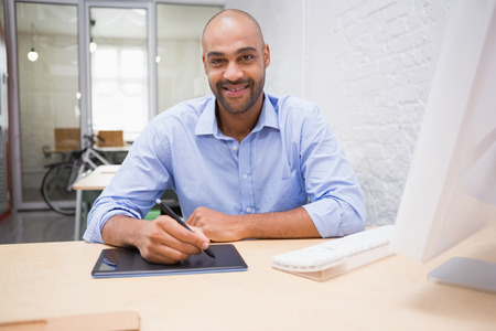 digitizer: Portrait of young man working at desk with computer and digitizer Stock Photo