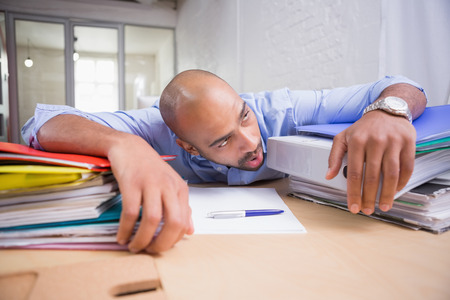 Tired young businessman with stack of files on office desk photo