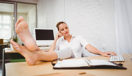 Relaxed young businesswoman sitting with legs crossed at ankle on office desk