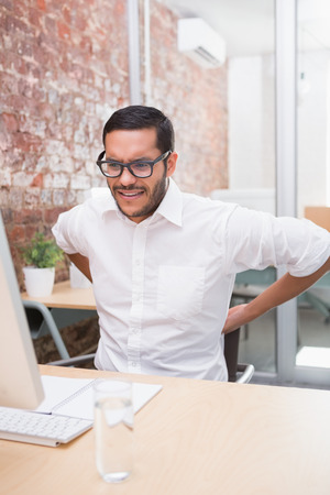 Young businessman suffering from backache at office desk photo