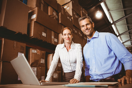 Portrait of warehouse manager and colleague using laptop
