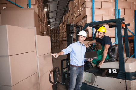 Warehouse manager talking with forklift driver in warehouse photo