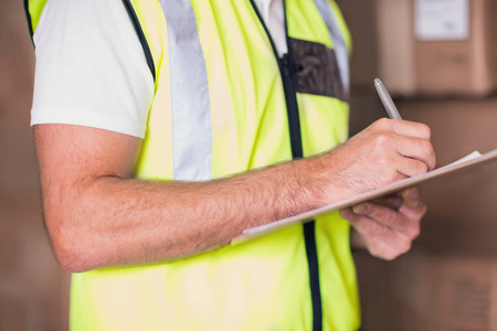 Close up mid section of warehouse worker with clipboard in warehouse photo