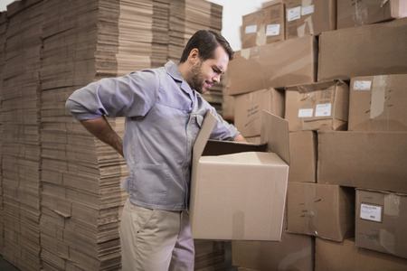 wincing: Side view of worker carrying box in the warehouse Stock Photo