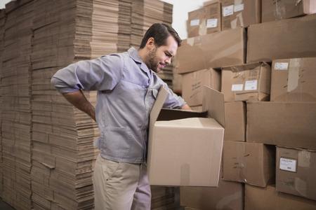 detras de: Vista lateral del trabajador caja que lleva en el almacén