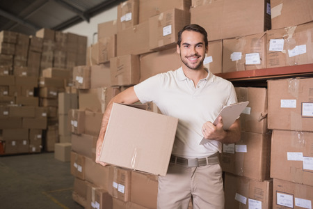 Portrait of smiling delivery man with box and clipboard in warehouse photo