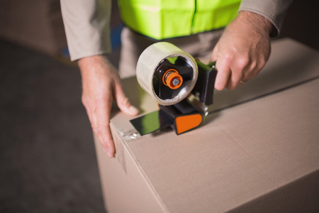 sealing tape: Close up mid section of worker in warehouse preparing goods for dispatch
