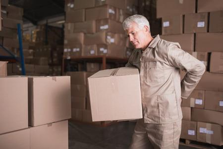 obrero trabajando: Vista lateral del trabajador con el dolor de espalda, mientras que la caja de elevaci�n en el almac�n