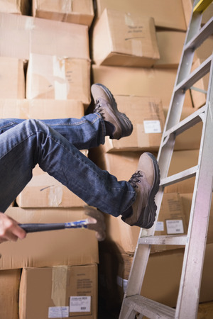 industrial accident: Low section of worker falling off ladder in the warehouse Stock Photo