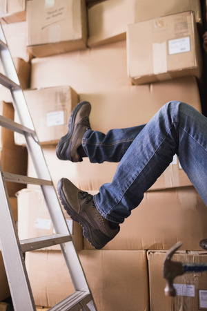 Low section of worker falling off ladder in the warehouse photo