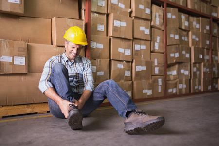 accidente laboral: Trabajador de sexo masculino sentado con esguince de tobillo en el piso en el almac�n