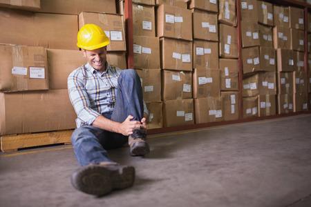 accidente laboral: Trabajador de sexo masculino sentado con esguince de tobillo en el suelo en almac�n