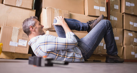 Side view of male worker lying on the floor in warehouse photo