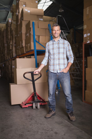 Portrait of worker with trolley of boxes in warehouse photo