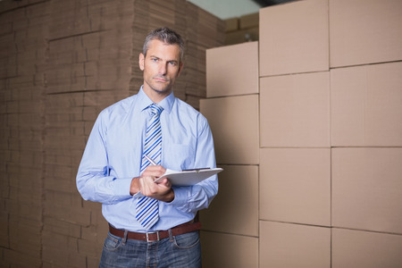 Portrait of manager holding clipboard against boxes in the warehouse photo