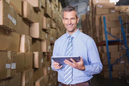 leveringen: Portret van mannelijke manager te openen met digitale tablet in magazijn