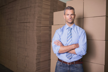 Portrait of serious male manager with arms crossed in warehouse photo