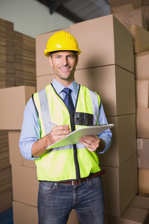 Portrait of warehouse worker with clipboard in warehouse photo