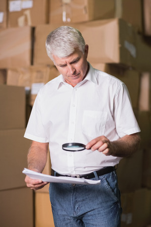 Manager looking at documents through magnifying glass in warehouse photo