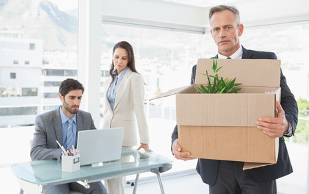 he old: Businessman leaving his old job as he has been fired Stock Photo