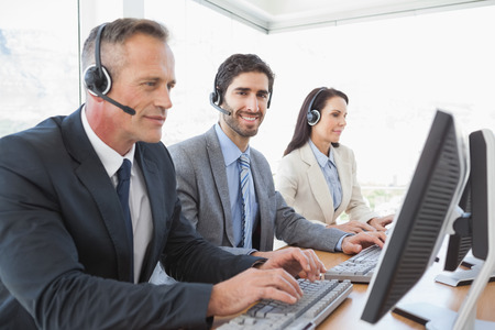 A business team working together at a call center wearing headsets photo
