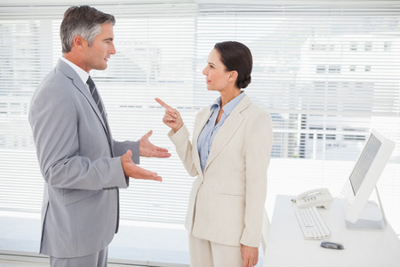 office attire: Businesswoman arguing with co worker in her office Stock Photo