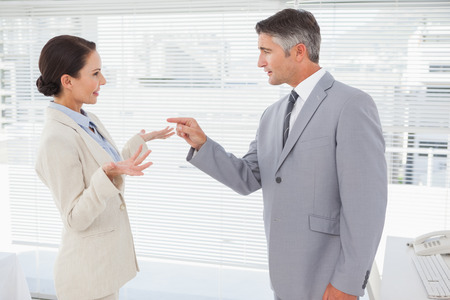 Businessman scolding his co worker at work photo