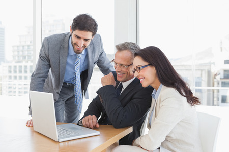reunion de trabajo: Equipo disfrutando de un video sonriente en un ordenador port�til en el trabajo