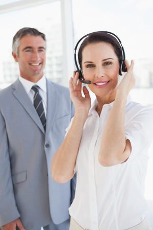 Businesswoman wearing a headset with co worker behind her photo
