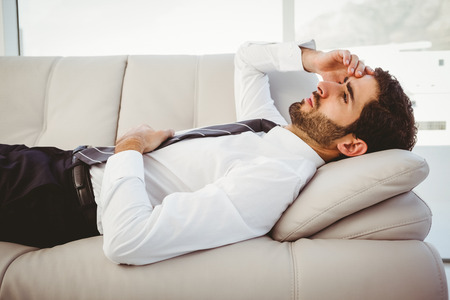 young adult: Sick businessman lying on the couch massaging his head Stock Photo
