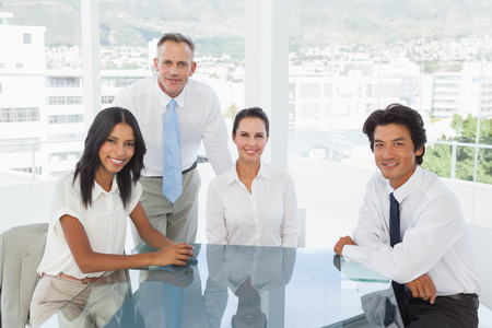 Smiling business team in an office looking at the camera photo