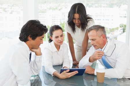 Business team looking at a tablet in work photo
