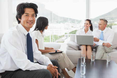 Smiling businessman with work colleagues sitting together photo