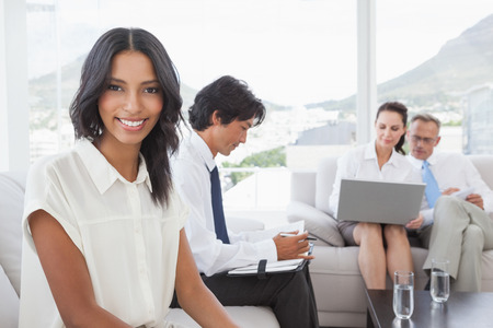 Smiling businesswoman with work colleagues sitting together photo