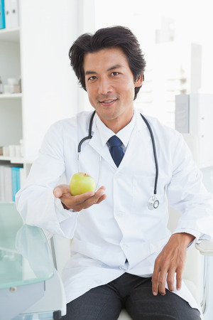 Happy doctor sitting at his desk holding an apple photo