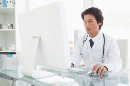 Serious doctor using the computer at work photo