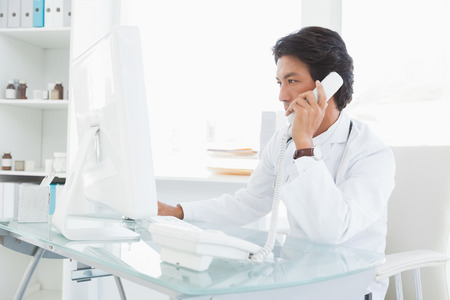 Doctor making work phone calls in his office photo