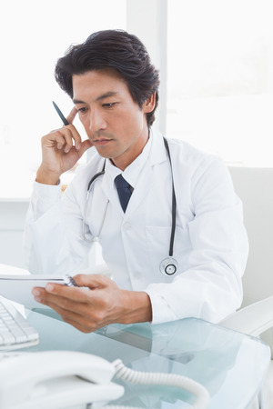 Serious looking doctor reading notes at his desk photo