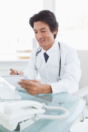 Happy doctor writing down notes at his desk photo