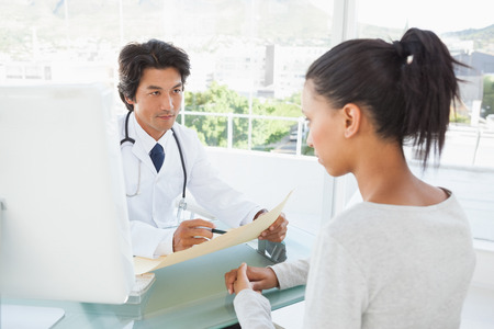 serious doctor: Doctor telling patient her results from her files Stock Photo