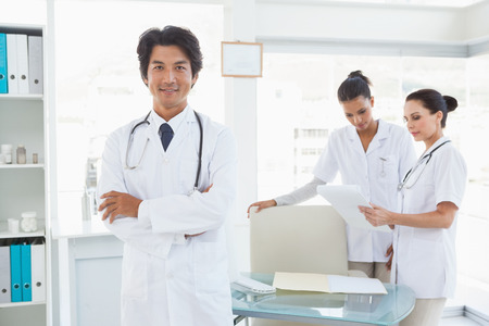 Doctor smiling in front of work colleagues in the office photo