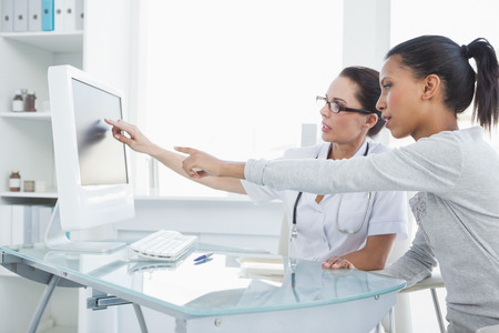 Doctor showing patient results on the computer in the office