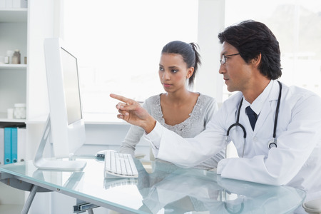 Doctor explaining results to his patient on his computer Stock Photo
