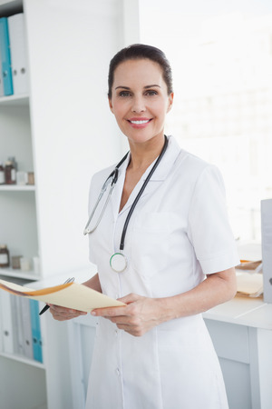 Happy doctor holding a medical file in her office photo