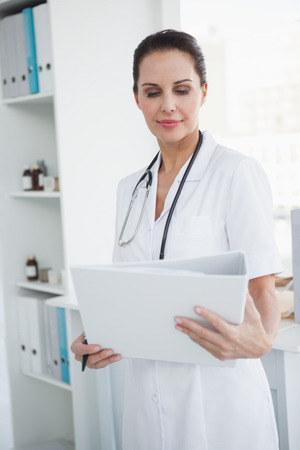 Focused doctor looking at a medical folder  photo