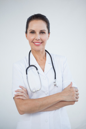 Smiling doctor looking at camera with folded arms photo