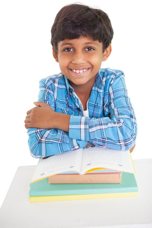 Cute elementary pupil smiling at camera on white background Stock Photo