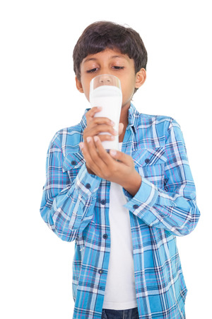 out in town: Cute boy drinking glass of milk on white background